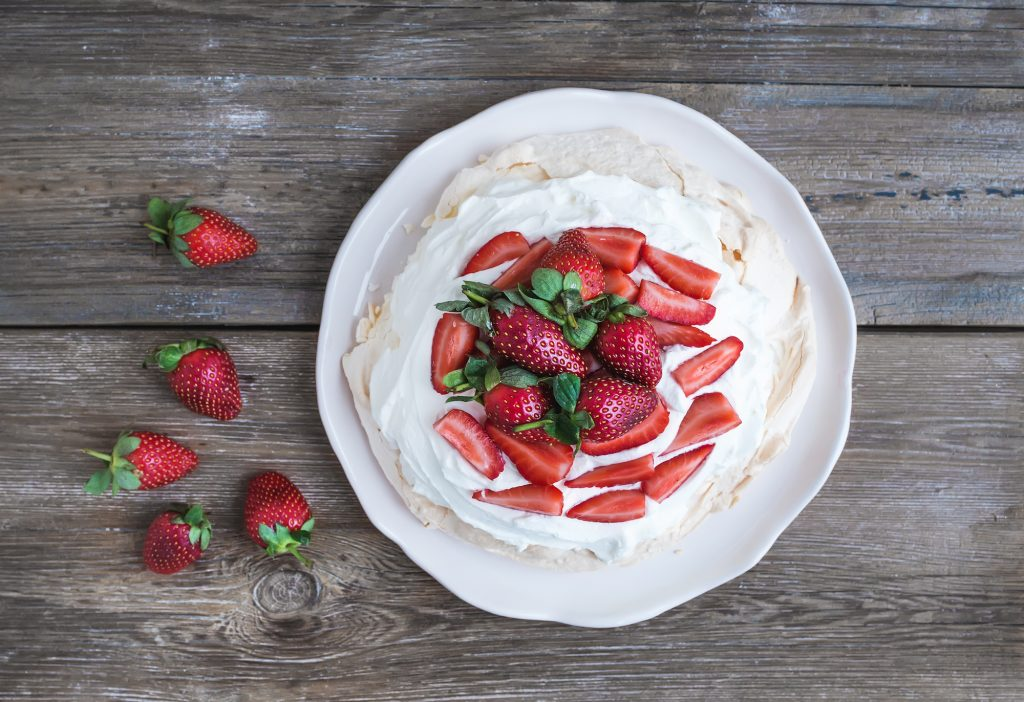 Rustic Pavlova cake with fresh strawberries and whipped cream over a rough wood background. Top view