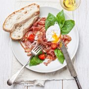 Ham salad with poached egg on white wooden background